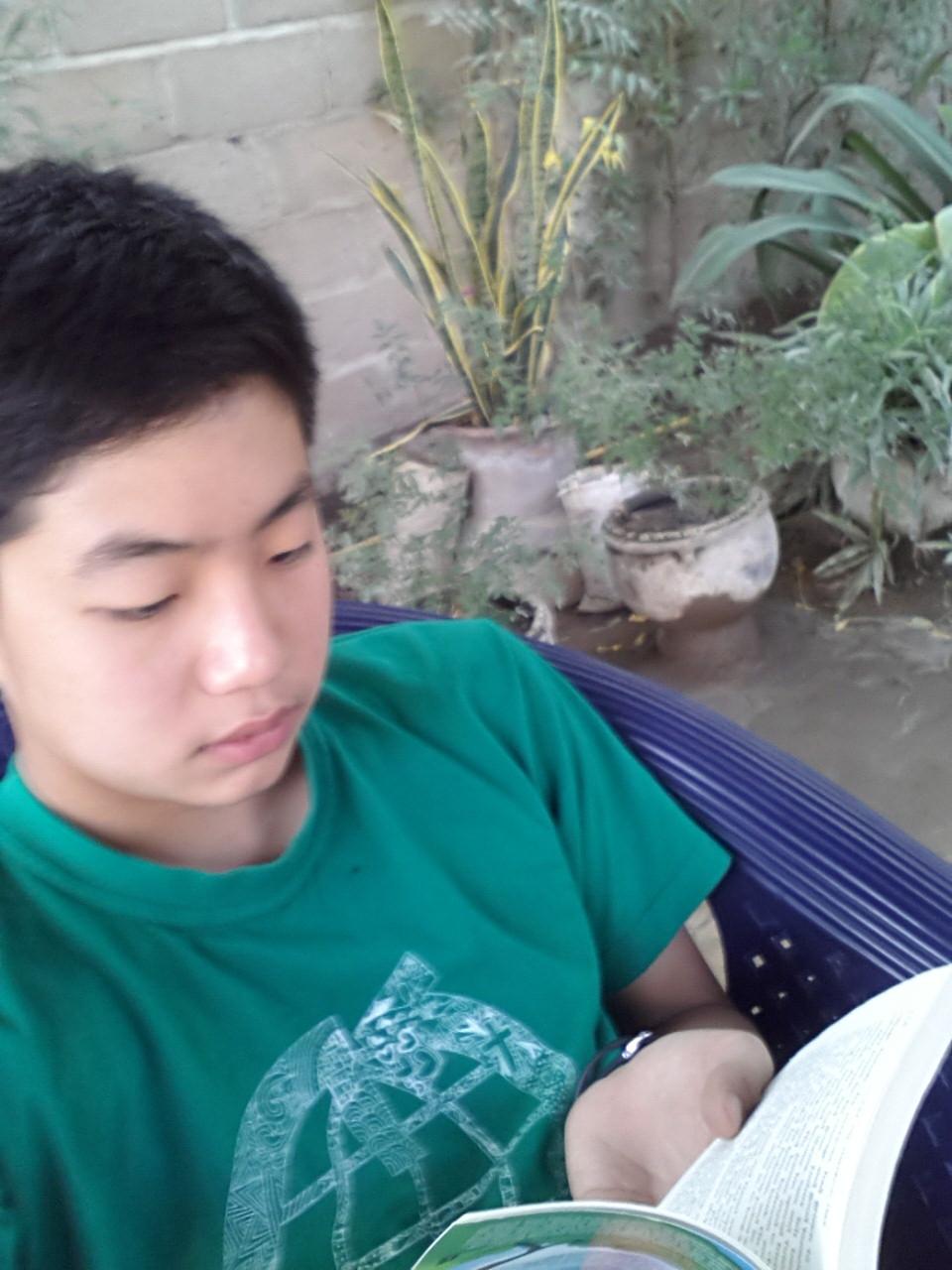 Korean lad reading Dernier book